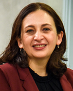 Portrait of Patty Alvarez wearing a black shirt with a maroon blazer