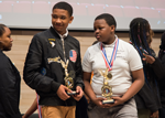 Khamari Stubbs (left), a Cohort 4 CURE Scholar, and Jaylen Galmore, a Cohort 3 CURE Scholar, accept their trophies for coming in first place at the 2019 CURE STEM Expo in the anatomy curriculum category.