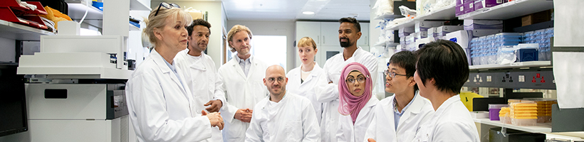 group of people discussing while wearing white coats in a lab