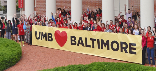 Staff holding a sign that says we love baltimore.