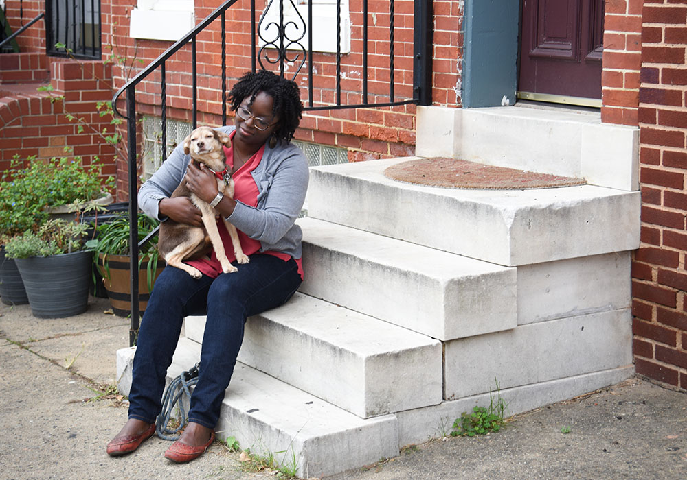 Khandra Sears and her dog on the porch of their Union Square home