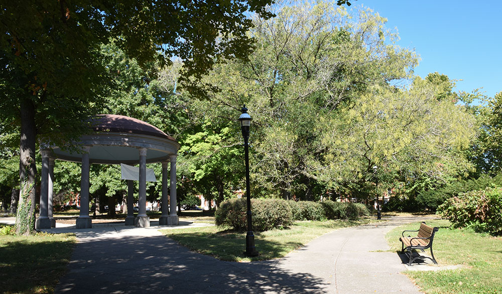 An arboreal park scene with a bench and gazebo