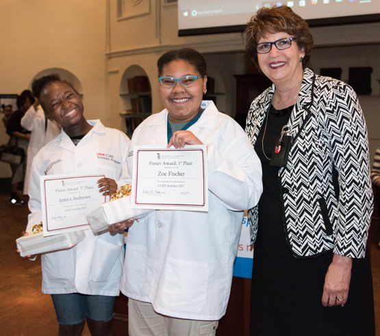 CURE Scholars Janiya Andrews, left, and Zoe Fisher hold first-place certificates awarded by Karen Faraone, DDS, MS, assistant dean of student affairs at the University of Maryland School of Dentistry and judge of the public health poster contest.