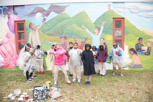 Fourth-graders from James McHenry Elementary/Middle School help paint a mural on their school thanks to UMB's Council for the Arts & Culture, which sponsored the artwork.