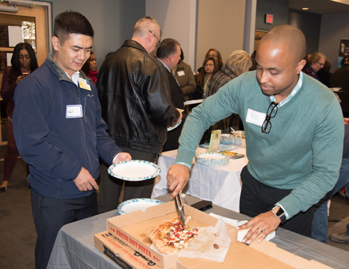 Bill Joyner, MSW, coordinator for UMB's Office of Community Engagement, serves Zella's pizza to Van Bik, a food and nutrition/sushi chef at University of Maryland Medical Center, at the Local Food Connection Fall Food Fair.