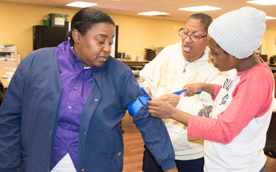 Annie Coples lends her arm to Jeanette Snowden and Sharina Thompson, who were practicing using a tourniquet at a Stop the Bleed class at UMB's Community Engagement Center.