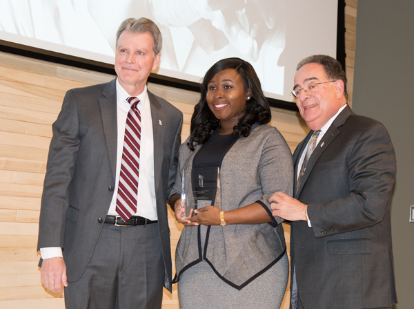 Tiffany C. Otto, a fourth-year dental student, received the Outstanding UMB Student Award for her work in the community and on campus furthering diversity. UM School of Dentistry Dean Mark A. Reynolds, DDS, PhD, left, assisted UMB President Jay A. Perman, MD, right, in the presentation.