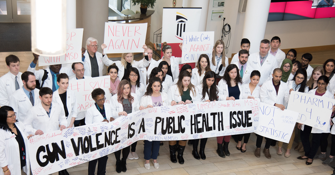 UM School of Pharmacy Dean Natalie Eddington, PhD, FAAPS, FCP, in the front row, third from left, stands next to student Allison Cowett of Parkland, Fla., who wears a green MSD High School shirt beneath a white coat, at a rally against gun violence held in the school's atrium.