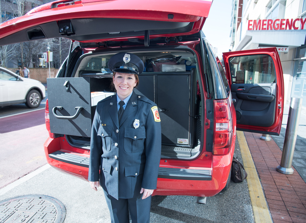 Jessica Thomas, CRT, a paramedic in the  Baltimore City Fire Department, is shown with one of two vehicles used in the MIH-CP program in West Baltimore.