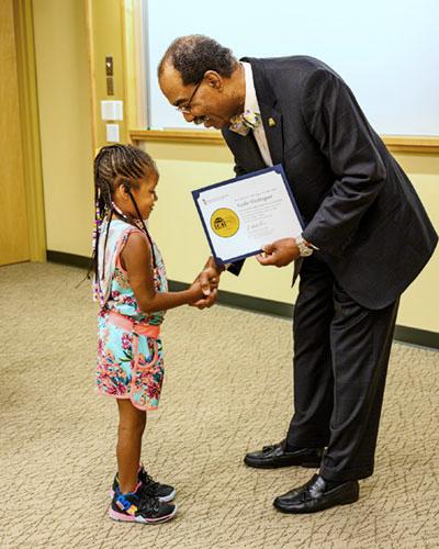 Dean E. Albert Reece presents a diploma at Mini-Med School for Kids.