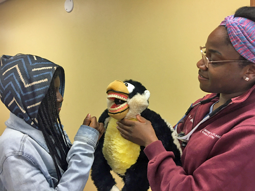 Using a puppet as a model, University of Maryland School of Dentistry student Ebbie Njoku teaches 10-year-old Taylor Sampson about flossing teeth at the University of Maryland, Baltimore's Second Annual Neighborhood Spring Festival on April 22.