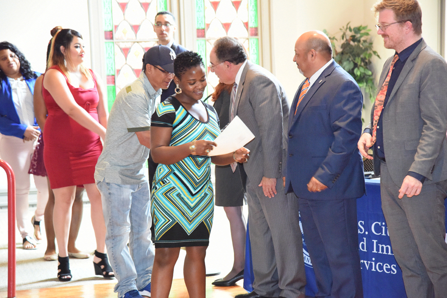 New U.S. citizen Endam Josephine Fombe, center, is greeted by, right to left, Luke Hall, section chief of U.S. Citizenship and Immigration Services (USCIS) Baltimore office; Conrad J. Zaragoza, field office director, USCIS Baltimore, and UMB President Jay A. Perman, MD, at the conclusion of a naturalization ceremony at Westminster Hall.