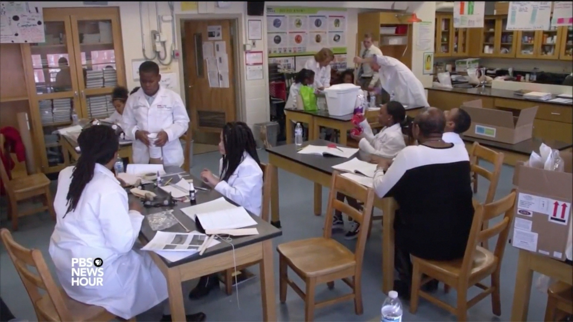 CURE Scholars at Franklin Square Elementary/Middle School work on science projects as shown in a video report by PBS NewsHour. Core team members for the CURE Scholars Program include Brian Sturdivant, MSW, far left, and Executive Director Robin Saunders, EdD, MS, mentoring a student at a table, far right.