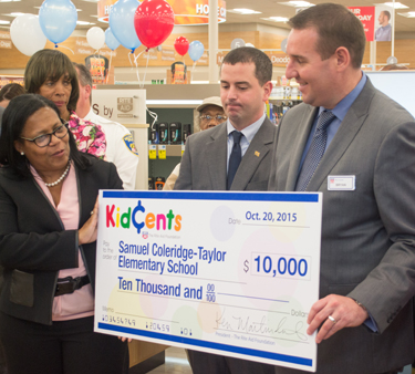 Principal Bettye M. Adams of The Historic Samuel Coleridge-Taylor Elementary School, which is among Promise Heights' Community Schools, accepts a donation. Rite Aid Executive Vice President of Operations Bryan Everett, right, is shown with Baltimore City Councilman Eric Costello, center, and Catherine Pugh, state senator (40th District), behind Adams.