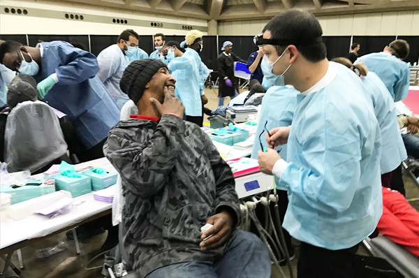 At a Mission of Mercy clinic during Project Homeless Connect, students from the University of Maryland School of Dentistry treat hundreds of patients, including Baltimore resident Ronald Ward, center, who describes his pain to Daniel DeCillis of the Class of 2018.