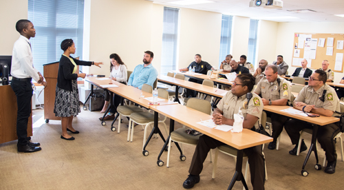 Taylor Owens of Baltimore Polytechnic Institute addresses UMB police officers on Zika virus issues as classmate Vernon Stepney looks on.