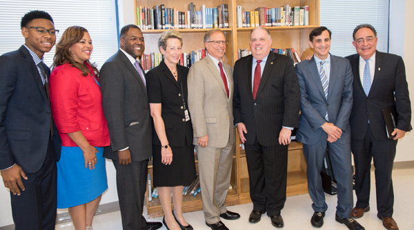 Standing left to right are Brooklyn, NY P-TECH graduate Radcliff Sadler, Maritha Gay of Kaiser Permanente, Baltimore City School Board Chair Marnell Cooper, Acting State Superintendent of Schools Karen Salmon, Stanley Litow of IBM, Governor Larry Hogan, Johns Hopkins President Ronald Daniels, and UMB President Jay Perman.