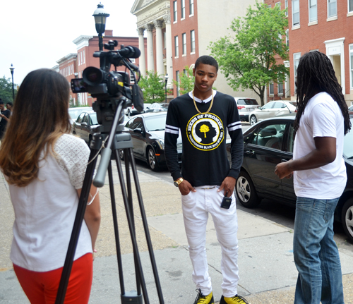 Khalil Bridges and Antwon Cooper of the Seeds of Promise mentoring program, right, are interviewed by WMAR-TV reporter Mallory Sofastaii outside Renaissance Academy, which is among the University of Maryland School of Social Work community schools.