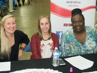 Center for Urban Families client service coordinator Kari Price, left, and School of Social Work students Alyssa McCreary, center, and Fatima Askew, right, offer resources to participants at Project Homeless Connect.