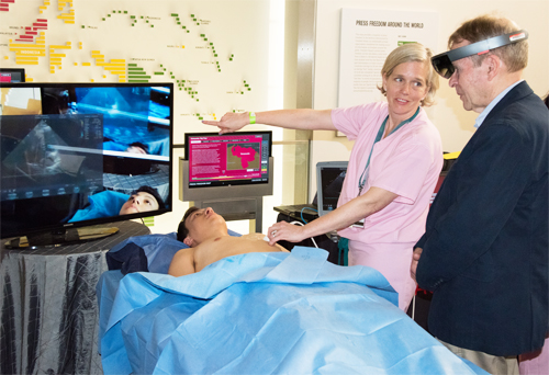 "Sarah Murthi, MD explains the augmented reality technology used to perform an ultrasound scan on volunteer ""patient"" Eric Lee."