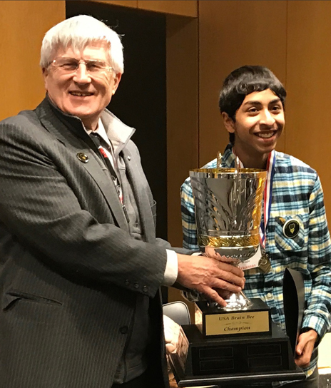Brain Bee founder Norbert Myslinski, PhD, associate professor at the University of Maryland School of Dentistry, presents a trophy to 2017 USA champion Sojas Wagle of Little Rock, Ark.