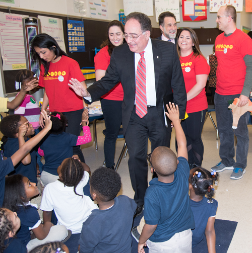 "UMB President Jay A. Perman, MD, greets kindergartners participating in an after-school wellness program at Furman L. Templeton Preparatory Academy. Students from UMB (shown in red shirts) have been trained as ""health leaders"" to teach the children about the importance of healthy eating and physical exercise. School of Social Work Dean Richard P. Barth, PhD, MSW, also observed the class activity."