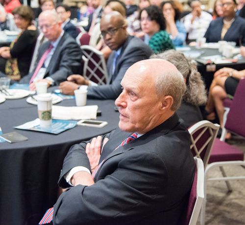 UMB Chief Academic and Research Ofcr. and Sr. VP Bruce Jarrell, MD, FACS, asks a question as Roger J. Ward, JD, MPA, Chief Accountability Ofcr. and Graduate School Vice Dean; Peter J. Murray, PhD, Chief Information Ofcr. and VP; and others look on.