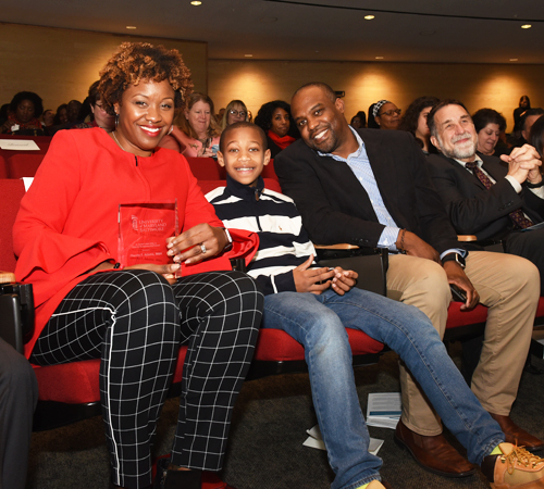 Cherita Adams, MBA, MS, and her family are all smiles after she was recognized with the Outstanding UMB Staff Award