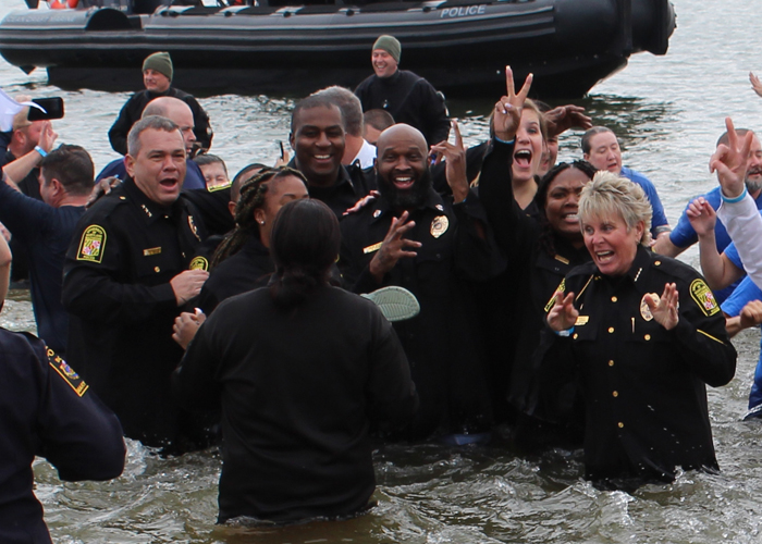 Chief Alice Cary (right) and other members of the University of Maryland, Baltimore Police Department plunge into the frigid waters of the Chesapeake Bay.