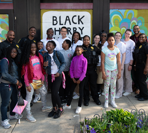 West Baltimore children, University of Maryland, Baltimore police officers and students from the University of Maryland School of Nursing stand outside the Black Cherry Puppet Theater after performing