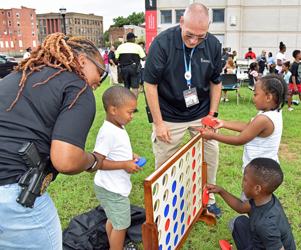Cpl. Hazel Lewis and Cpl. J.R. Jones play outdoor games with several West Baltimore neighbors.
