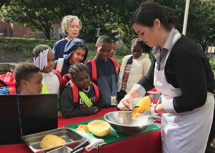 Third-grade students from Robert Coleman Elementary School watch a spaghetti squash cooking demonstration put on by CulinArt at the University Farmers Market.