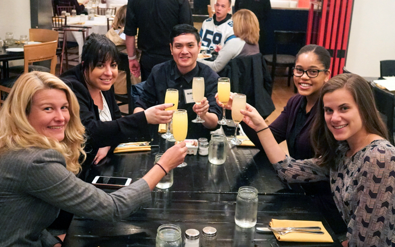 (From left) Erin Teigen, Adrienne Thomas, McMillan Ching, Dominique Earland, and Jenny Breau toast their victory after receiving the grand prize in the sixth annual D.C. Public Health Case Challenge. Team member Chigo Oguh is not pictured.