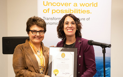 Marianne Navarro (right), representing the Mayor's Office of Neighborhood Development, presents Illumina vice president of Americas service and support Eleezeh Safarians with a citation on behalf of Mayor Jack Young.