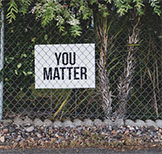 Image of sign behind fence that reads,