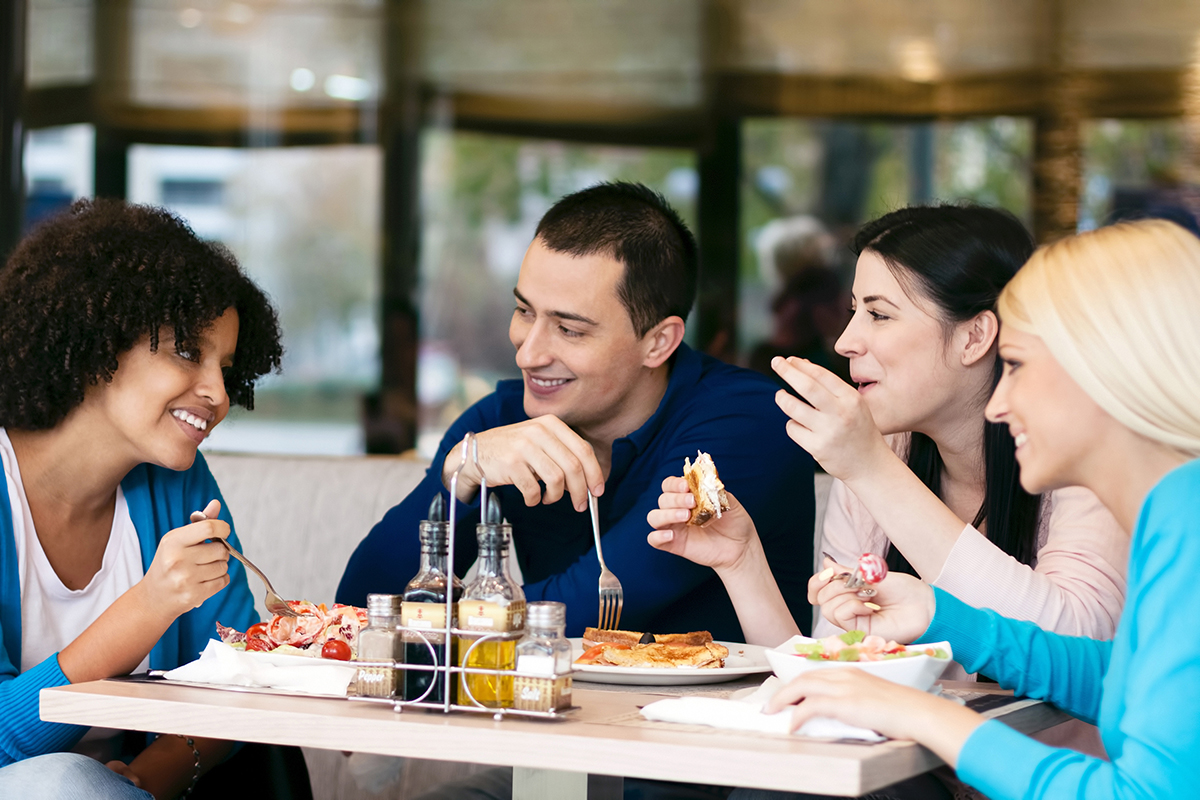 four people sitting around a table eating a meal