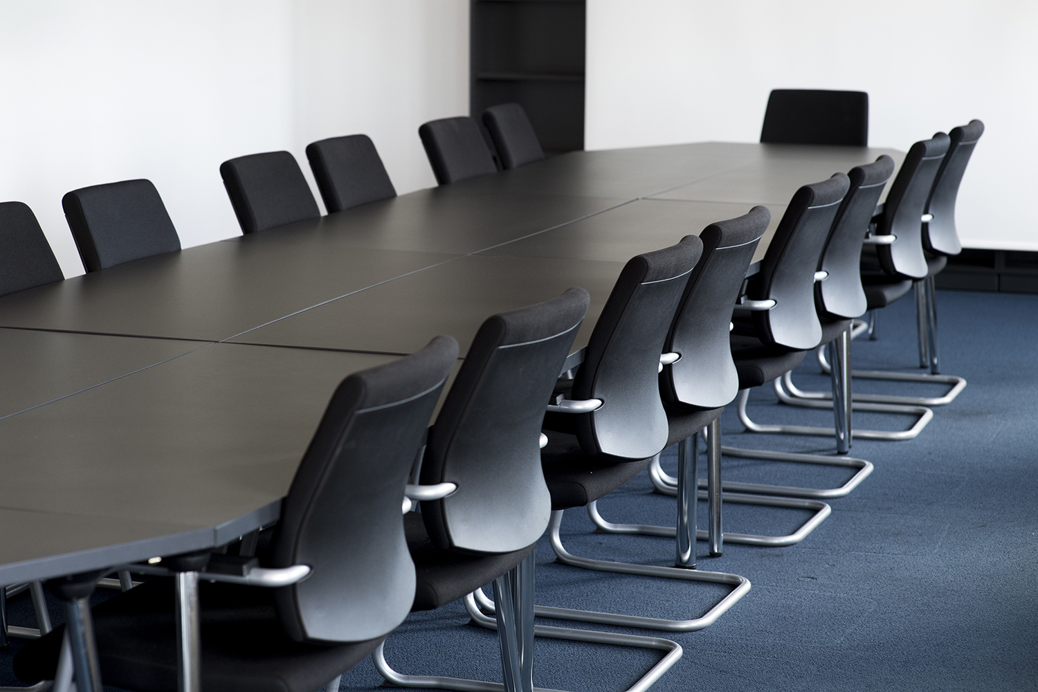 An image of a conference table and black chairs around it in a meeting room