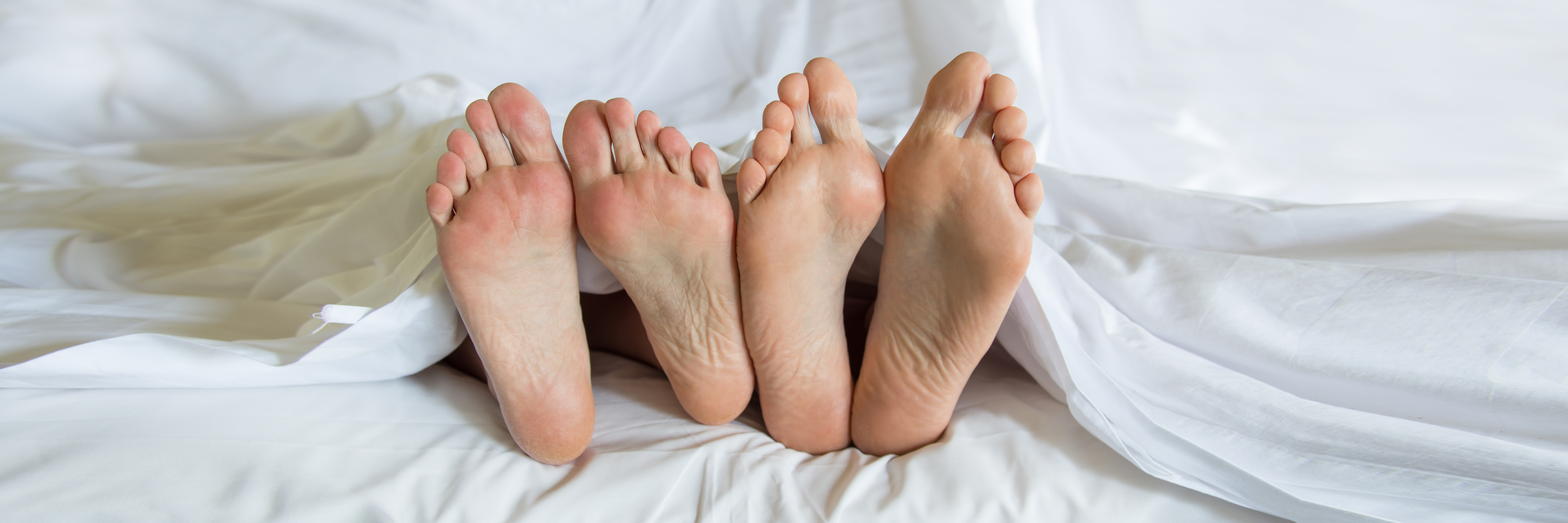 Two sets of feet in bed with white sheets