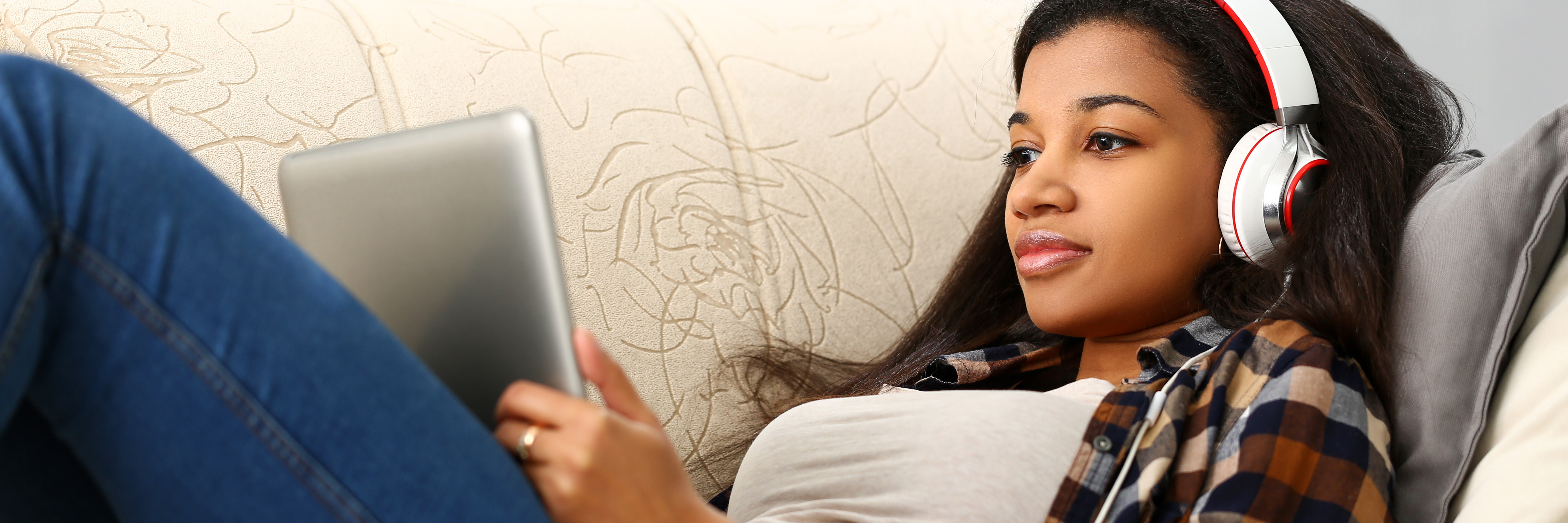 POC woman with headphones looking at IPAD