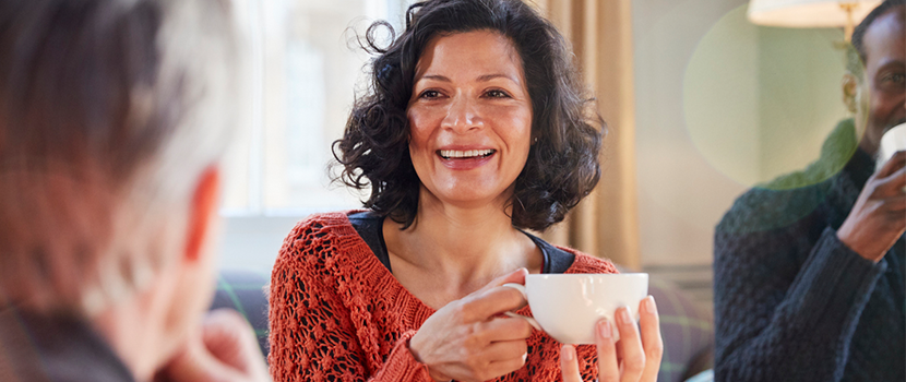 A stock image of a smiling woman in conversation with others.
