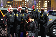 UMBPD Officers in Santa hats in front of a patrol vehicle
